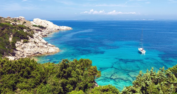 Blue sea and coast view with lonely yacht in Sardinia, Italy