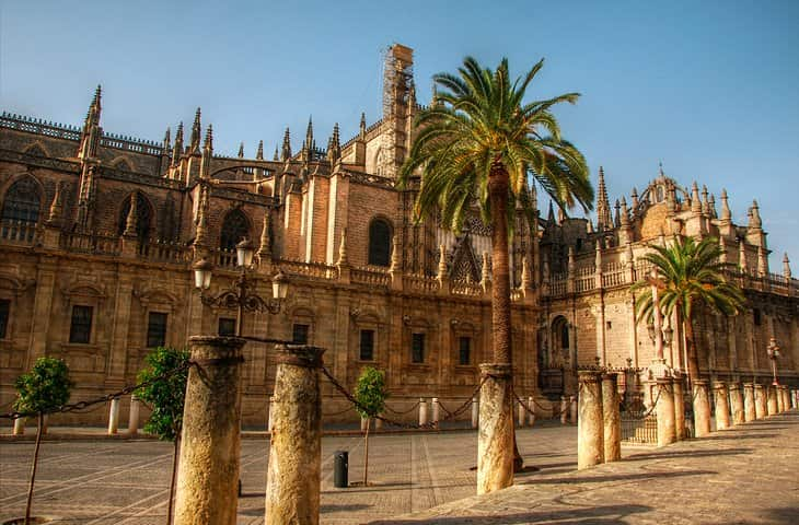 spain-seville-cathedral-and-palm-trees-min